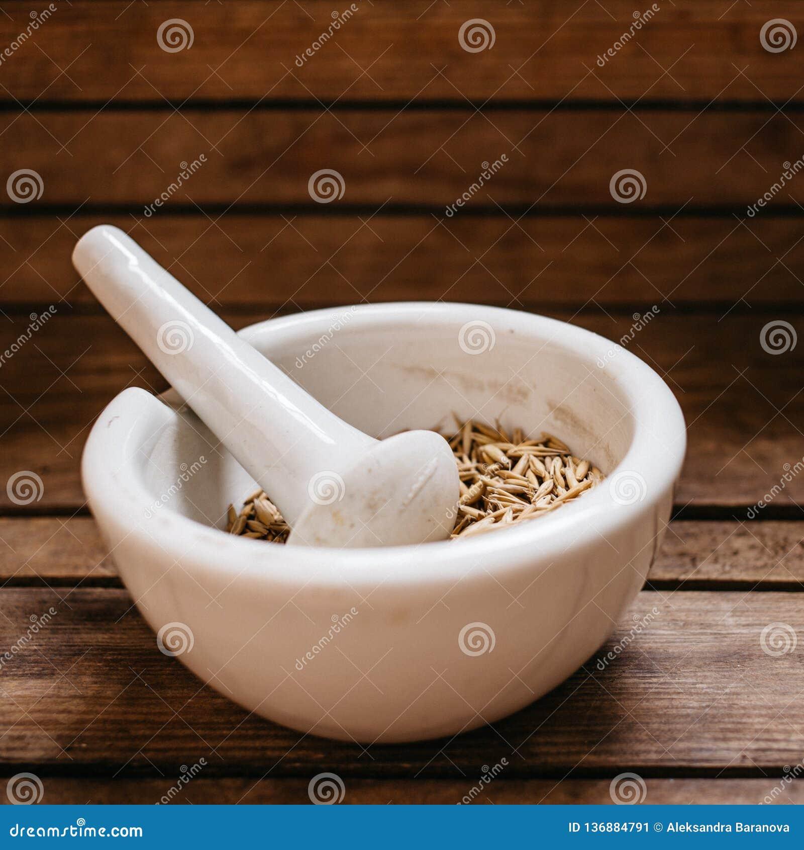 Vue supérieure des grains d avoine dans la cuvette de mortier de porcelaine sur la vieille table en bois
