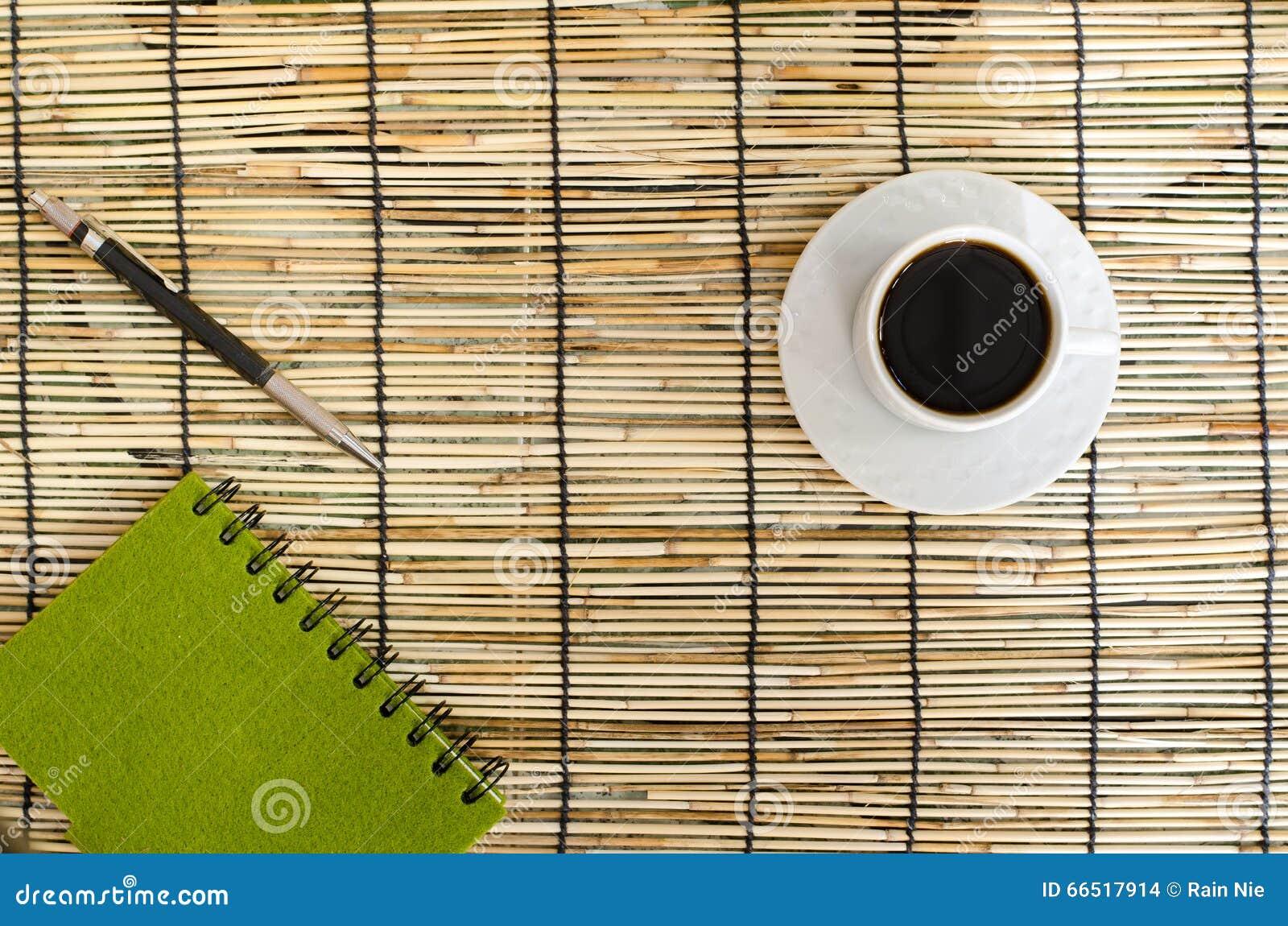 Vue supérieure des grains de café avec la tasse blanche, le carnet vert et le stylo sur le tapis
