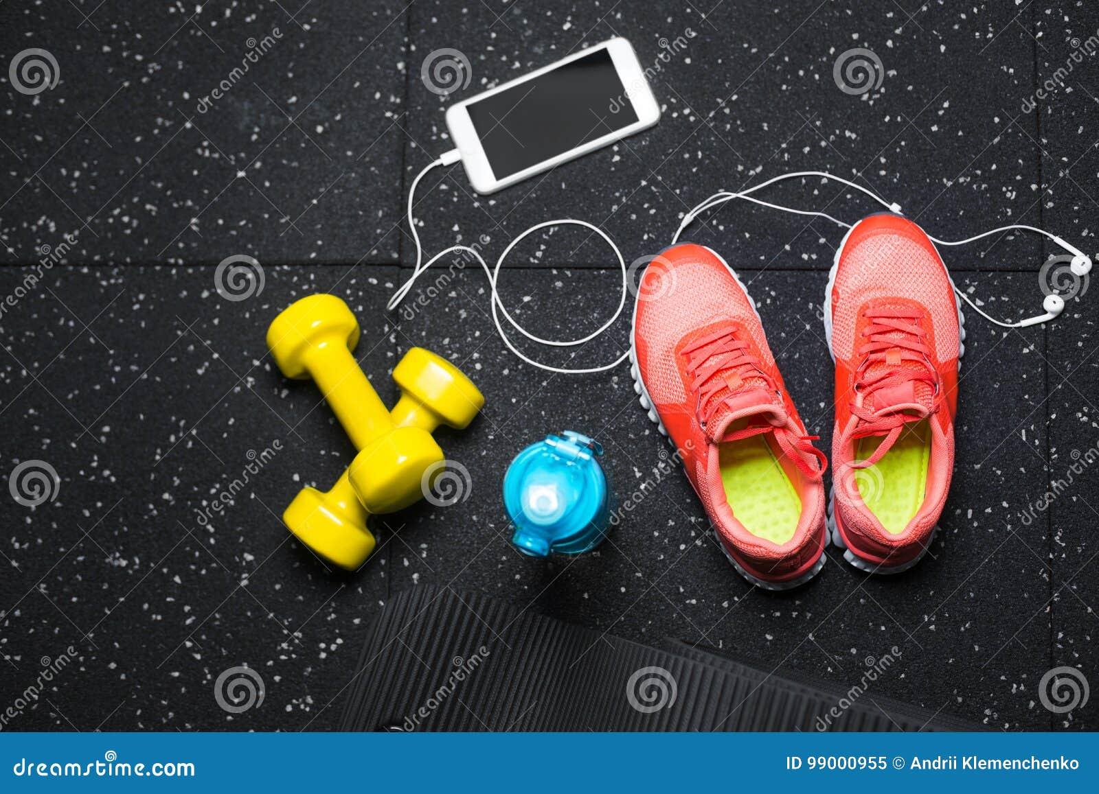 Vue supérieure des haltères jaunes lumineuses, d un tapis, de bouteille de l eau, de chaussures de sports et de téléphone sur un