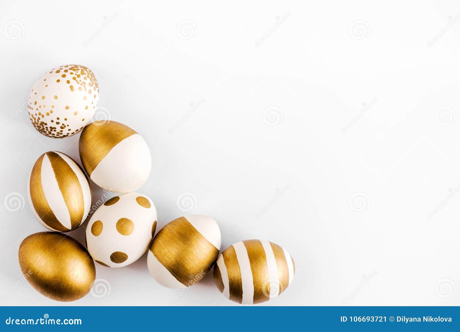 Vue supérieure des oeufs de pâques colorés avec la peinture d or Diverses conceptions rayées et pointillées Fond blanc