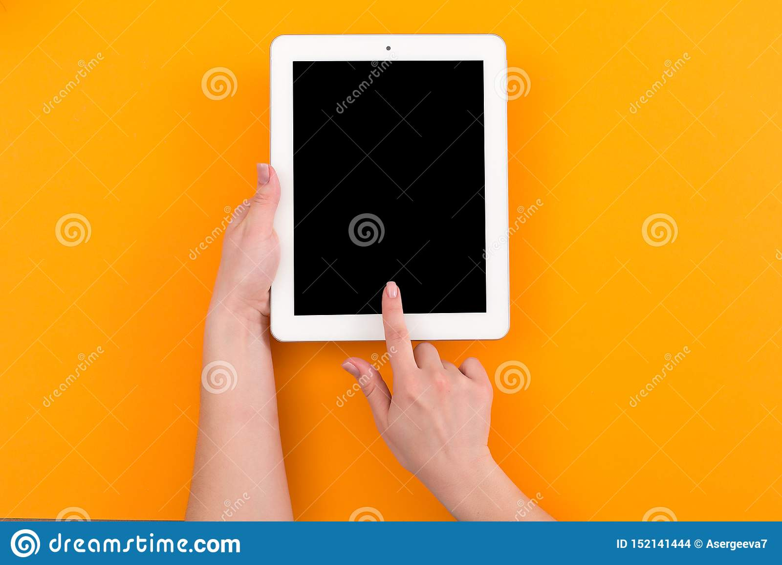 Vue supérieure en gros plan de femme tenant le comprimé numérique avec l espace de copie sur le fond orange
