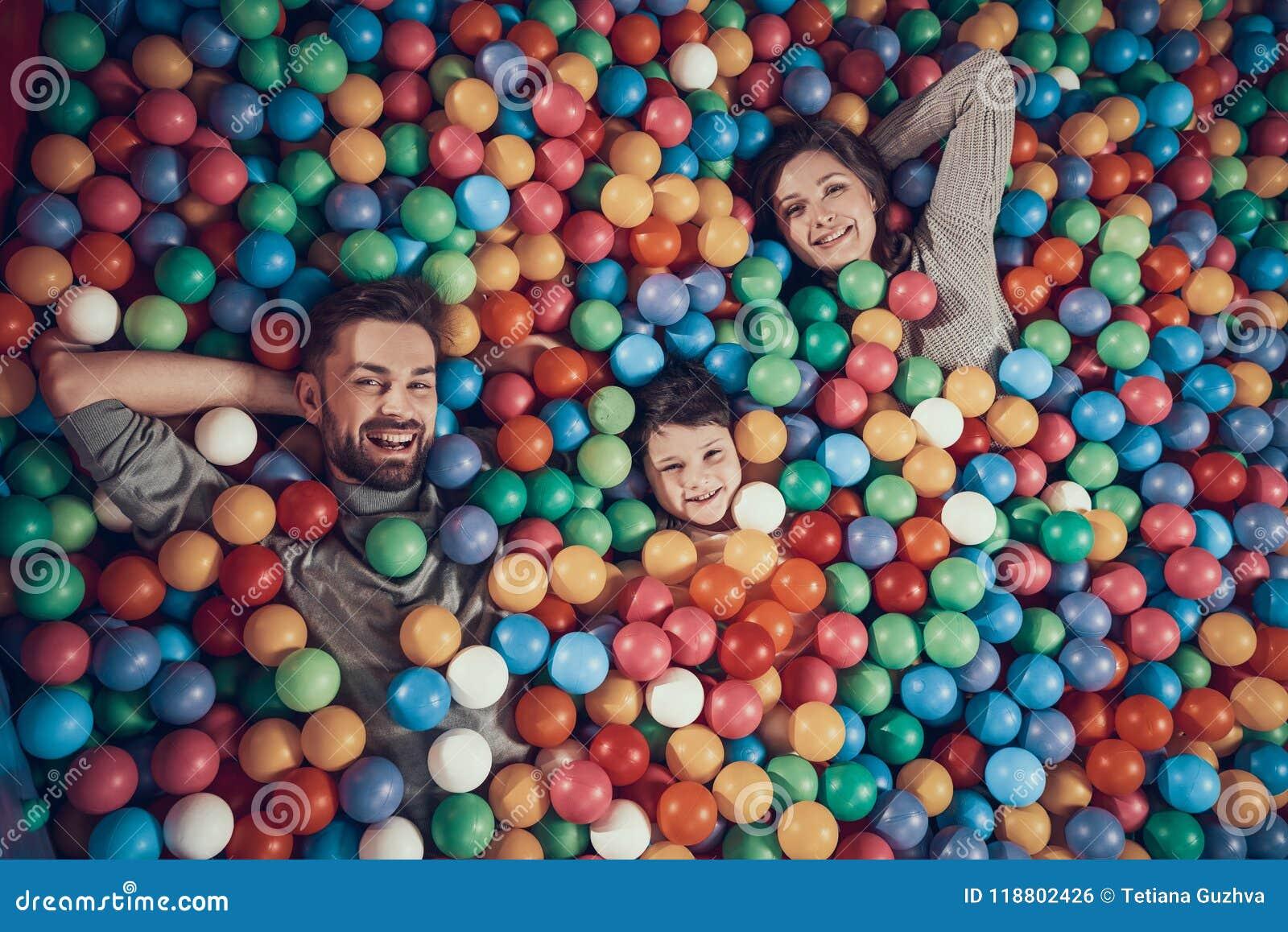 Vue supérieure Famille heureuse se situant dans la piscine avec des boules