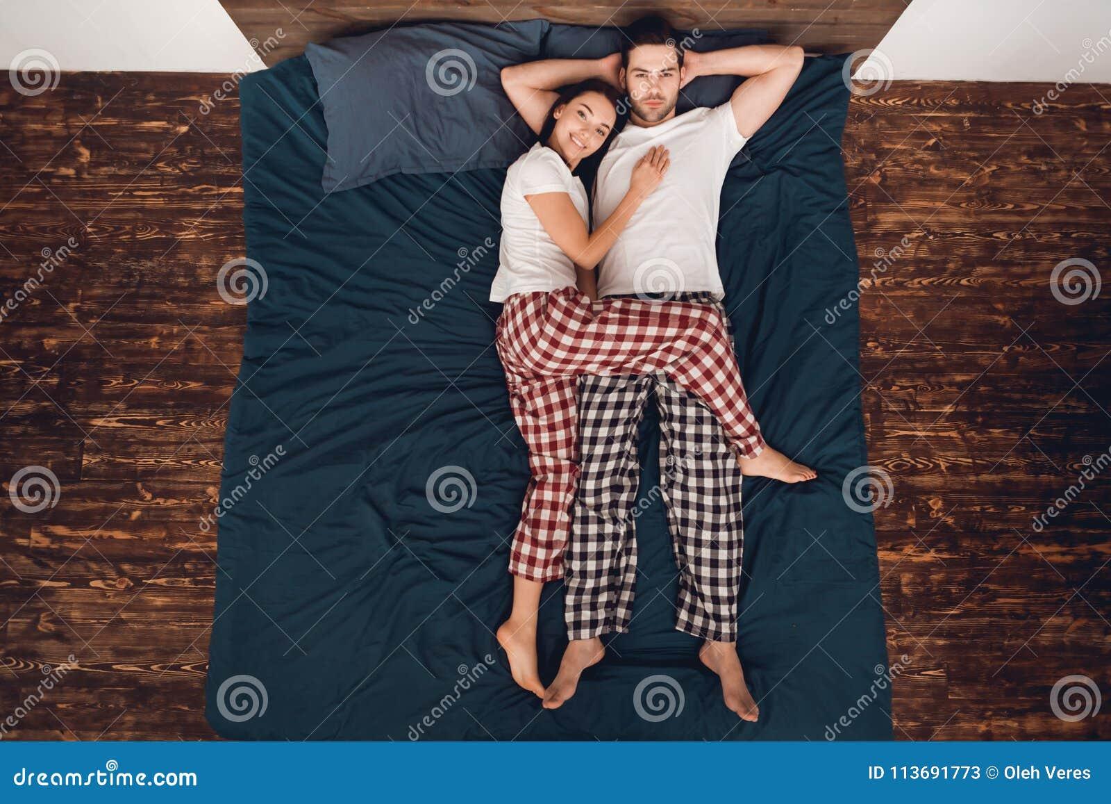 Vue supérieure La belle jeune femme se trouve à côté de l homme bel Poses de sommeil pour des couples