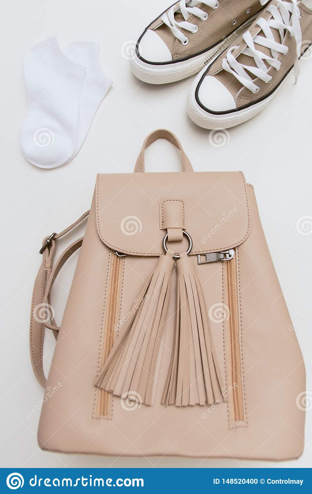 Vue supérieure sur les espadrilles brunes, sac à dos beige, chaussettes blanches sur le fond en pastel