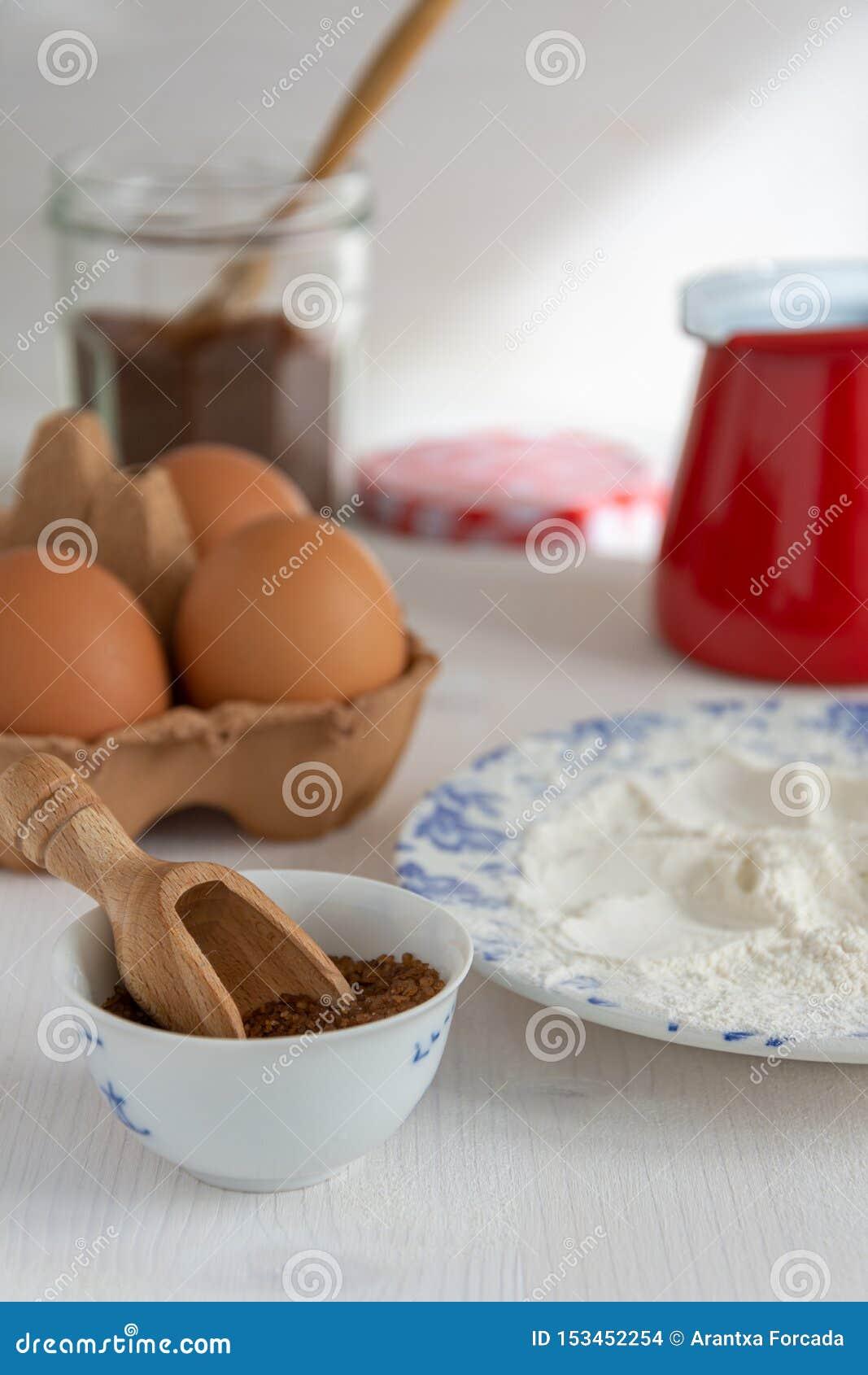 Vue supérieure verticale des ingrédients pour les pâtisseries, le sucre roux, la farine, les oeufs et la casserole rouge