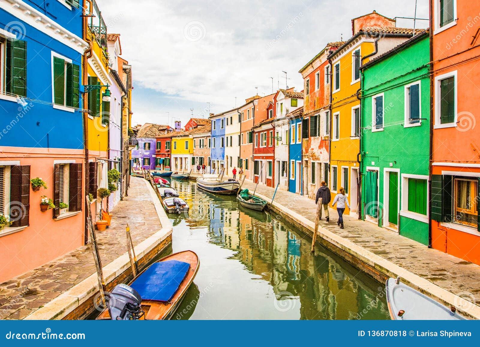 Vue sur la scène typique de rue montrant les maisons et les bateaux brillamment peints avec la réflexion le long du canal