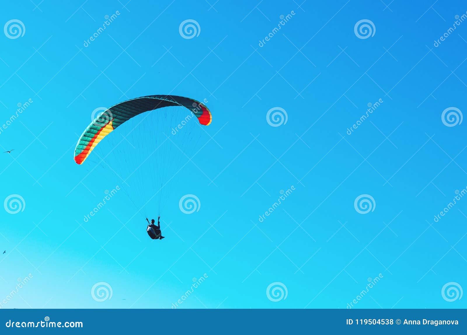 Vuelo del ala flexible en el paracaídas colorido en cielo claro azul en un día de verano soleado brillante Forma de vida activa,