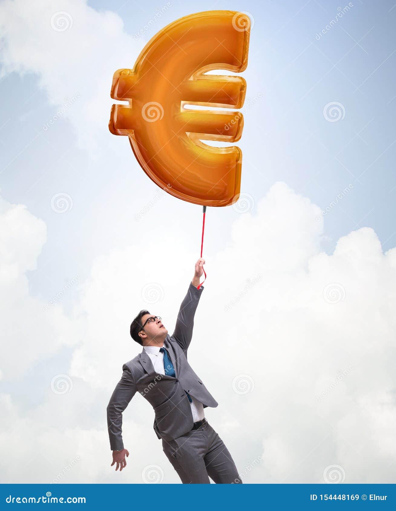 Vuelo del hombre de negocios en el globo inflable de la muestra euro
