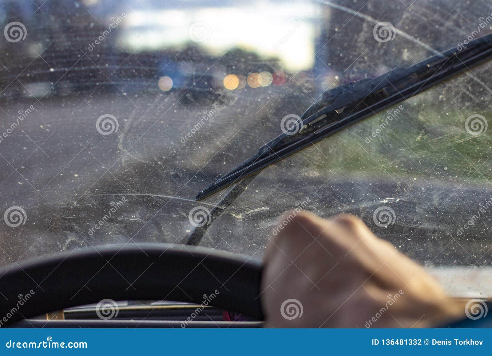 Vuil gekrast autowindscherm met wisser door vaag stuurwiel met de hand van de bestuurder op vage achtergrond