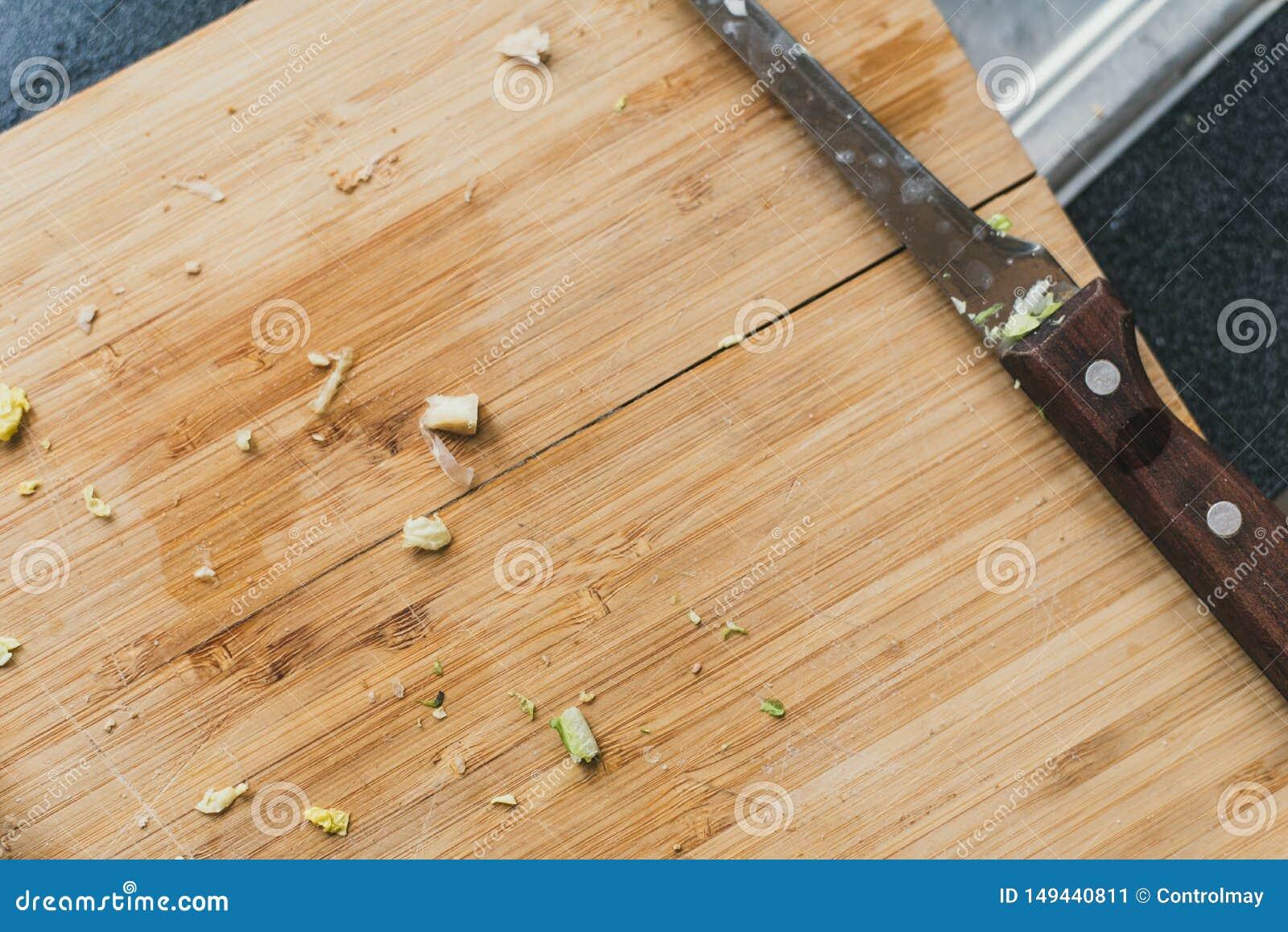 Vuile houten scherpe raad met een mes Uien op een scherpe raad worden gesneden die resten van groen op een houten achtergrond