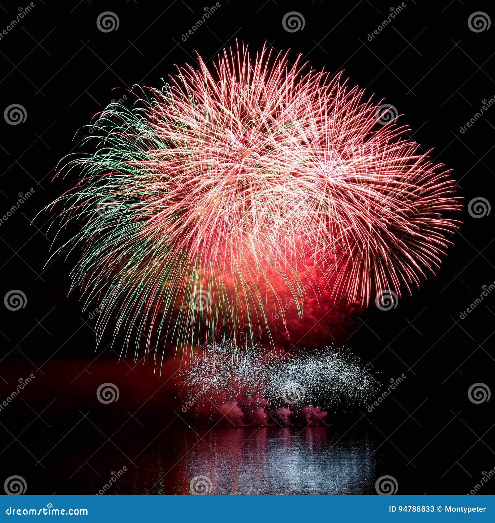 Vuurwerk Mooi kleurrijk vuurwerk op de waterspiegel met een schone zwarte achtergrond Pretfestival en wedstrijd van Brandbestrijd