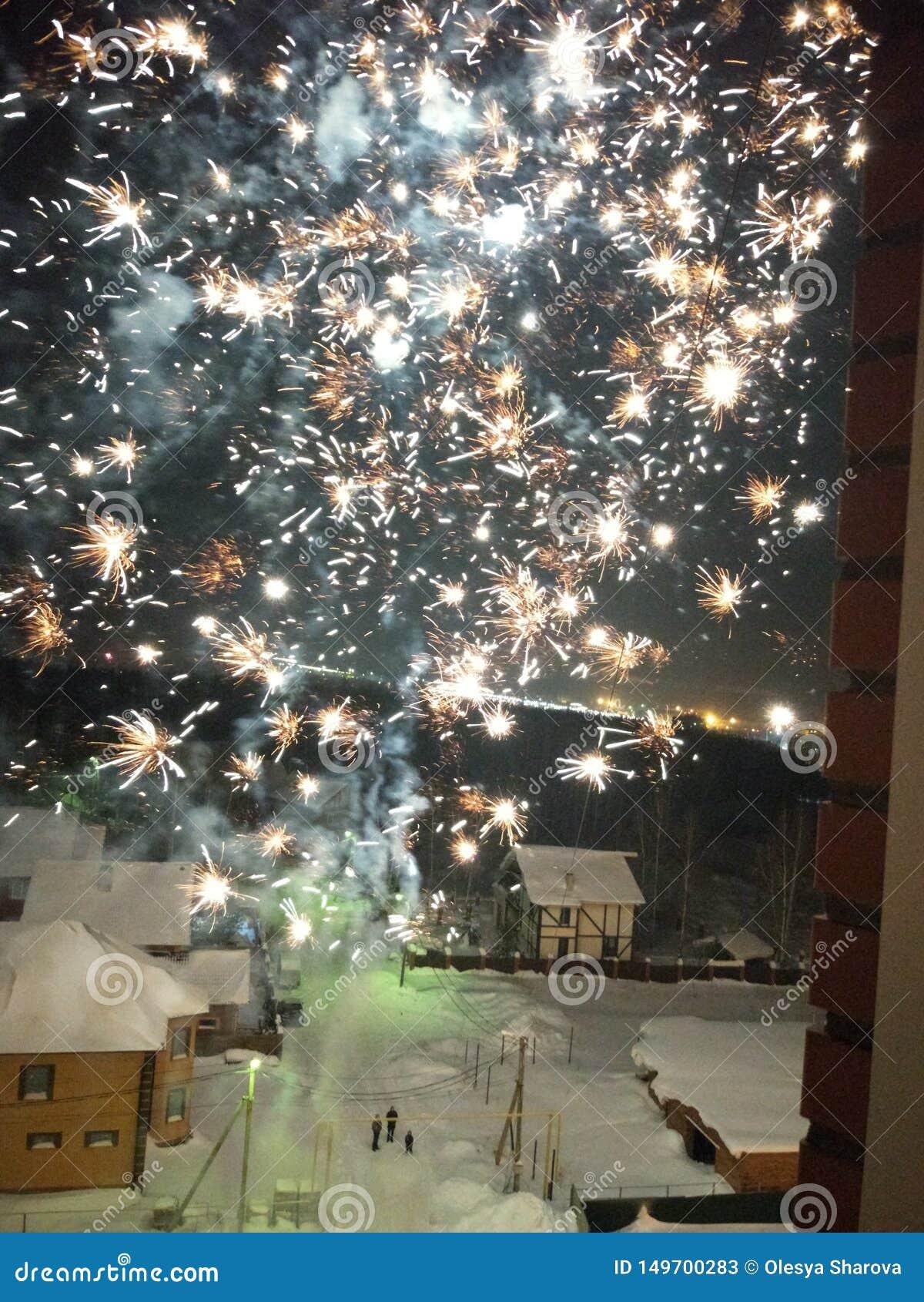 Vuurwerkuitbarstingen door het open venster op een de winternacht
