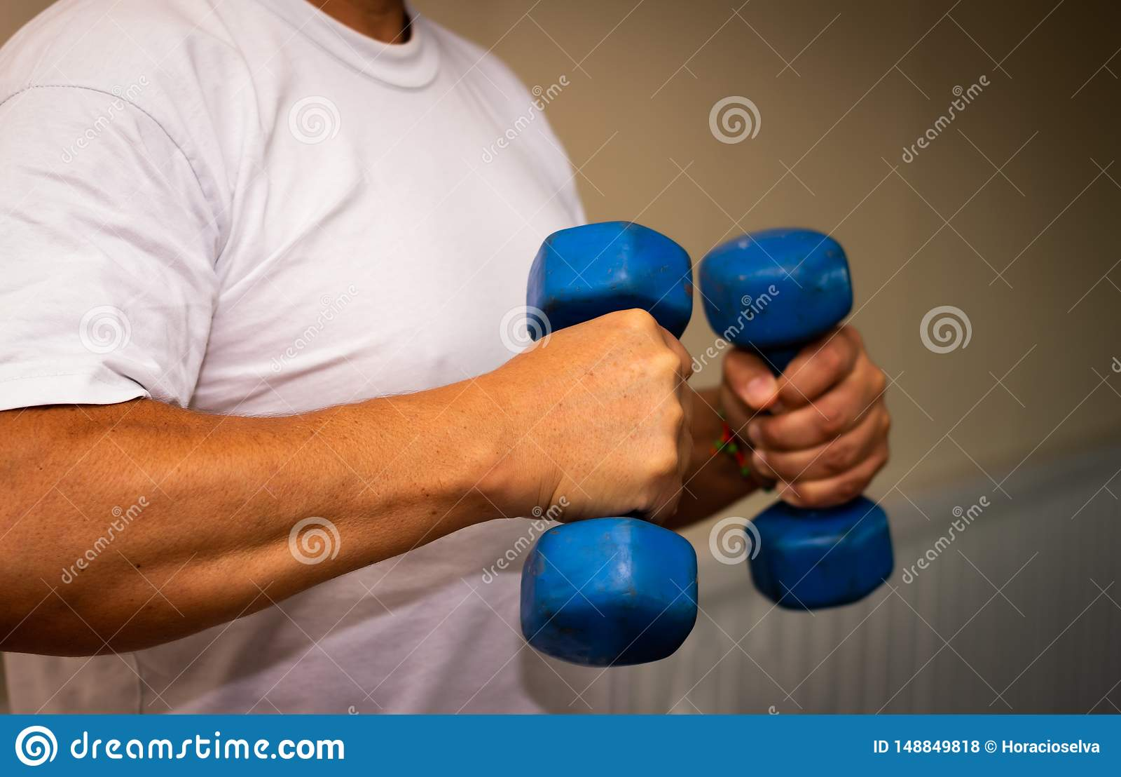 Vuxen man som g?r ?vning i idrottshallen Man med sm? bl?a vikter H?lso- och wellnessbegrepp
