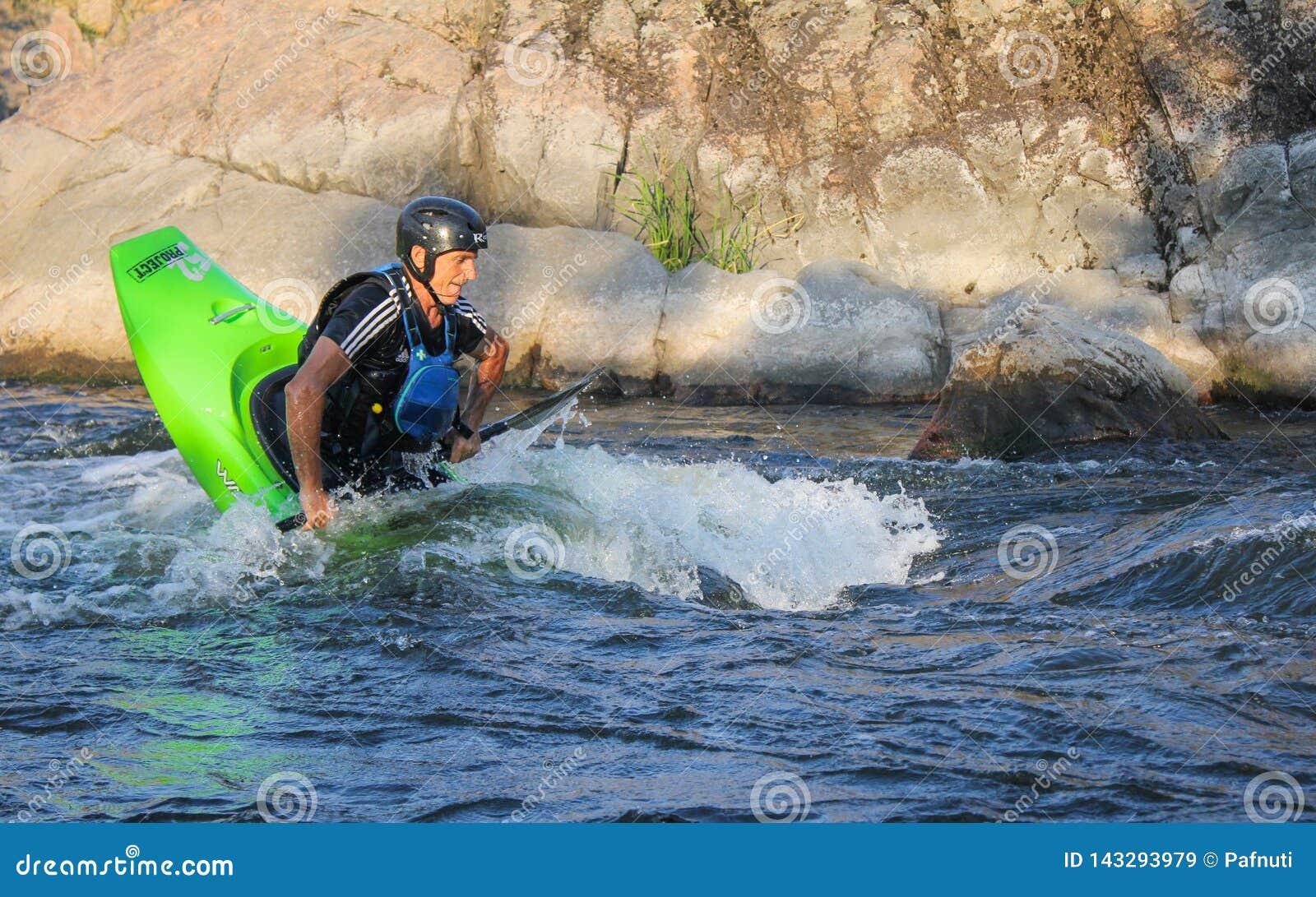 Vuxen man som paddlar en kajak på floden