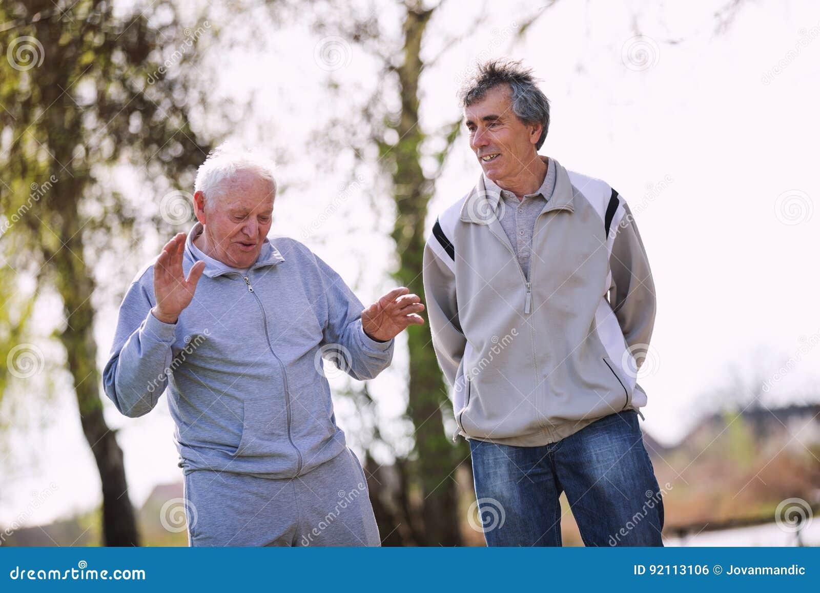 Vuxen son som går med hans höga fader