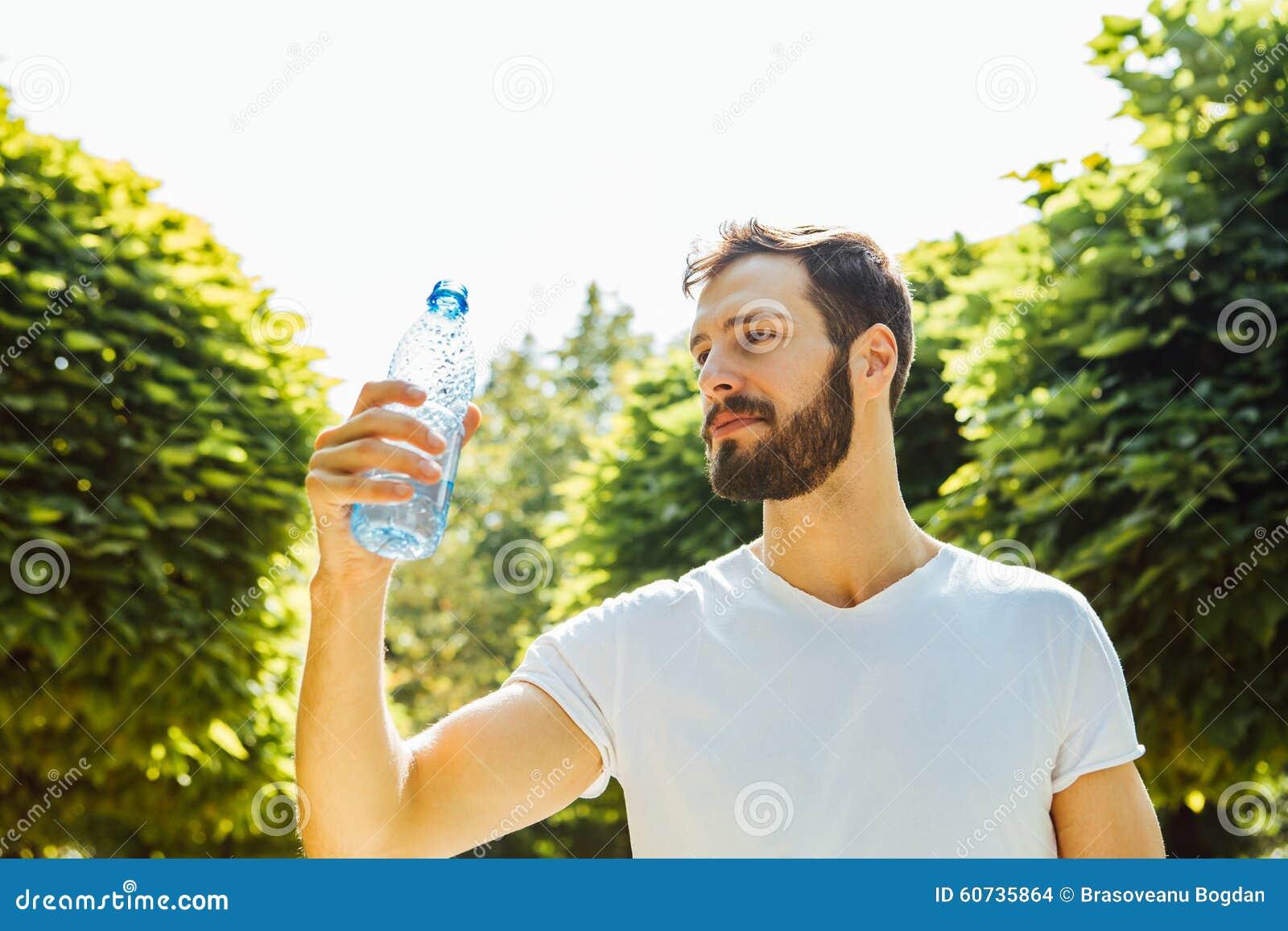 Vuxet mandricksvatten från en flaska utanför