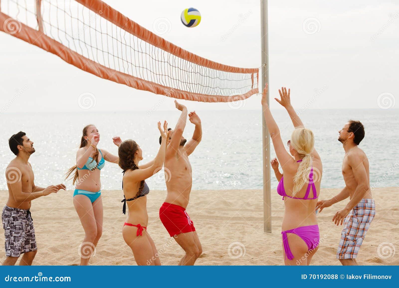 Vuxna människor som kastar bollen över netto och att skratta