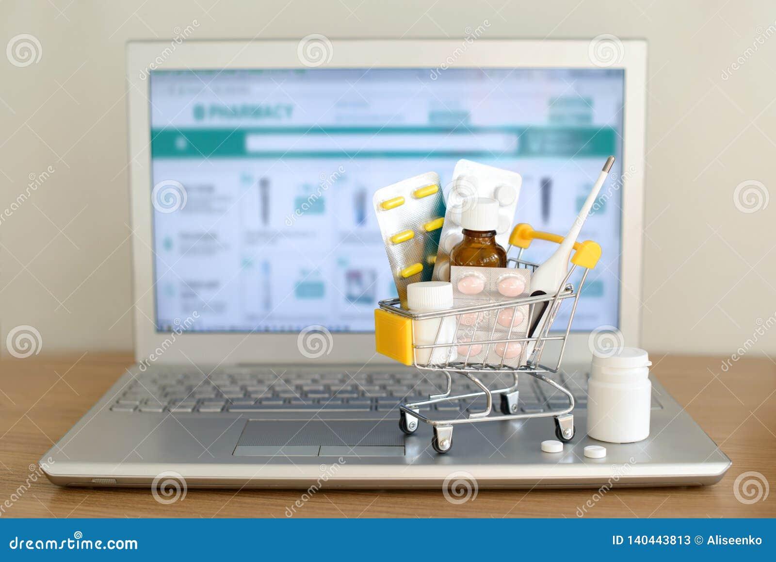 Wózek na zakupy zabawka z medicaments przed laptopu ekranem z apteki stroną internetową na nim Pigułki, bąbel paczki, medyczne bu