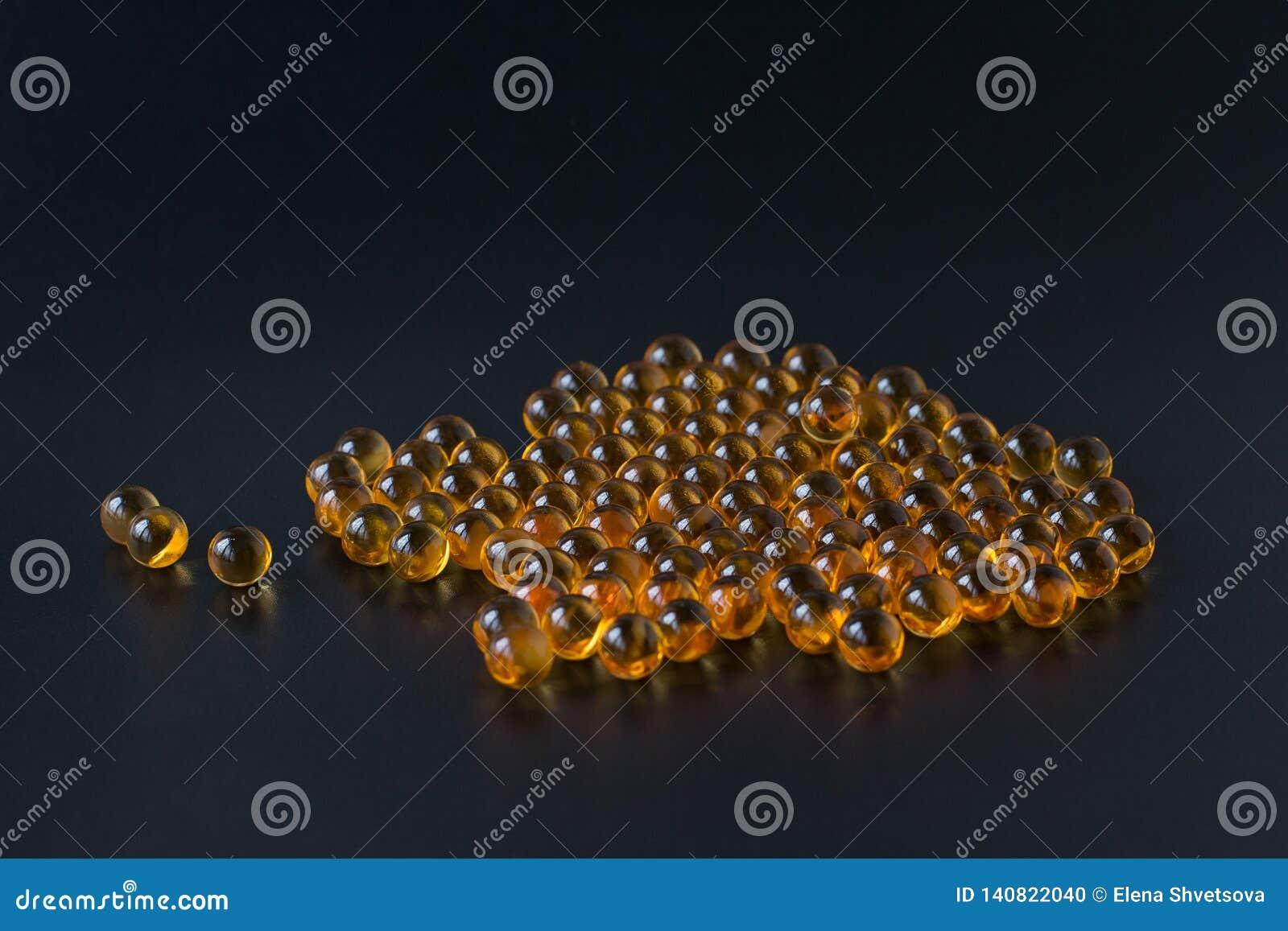 Wątróbka olej w kapsułach na czarnym tle