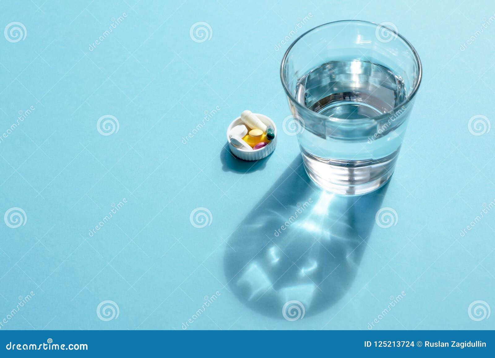 Wässern Sie in einer transparenten Glasschale und in einer Dosis von Tabletten im Deckel auf einer blauen Oberfläche