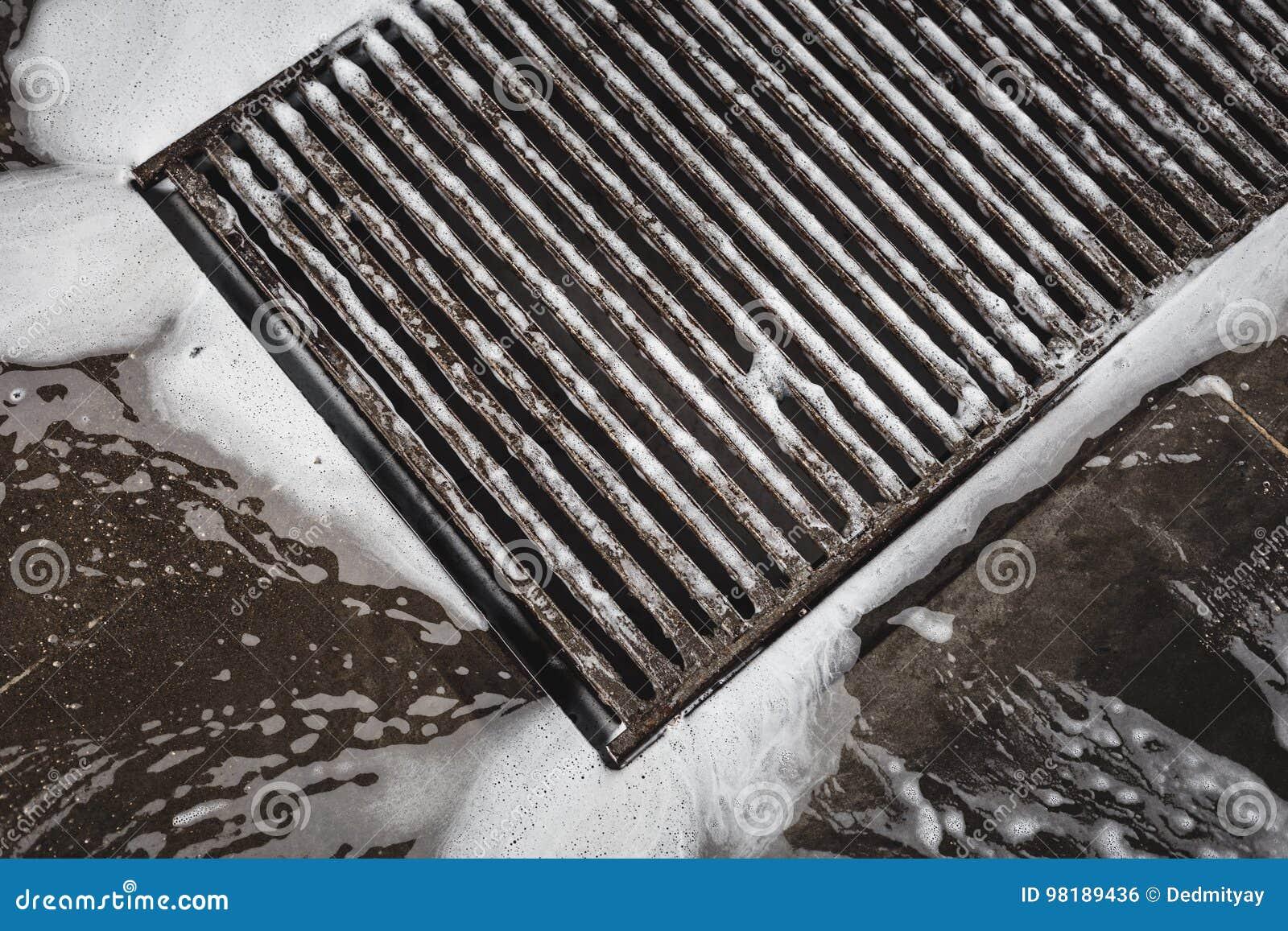 Wässern Sie Entwässerungsgrill auf der Waschanlage, den Schaum, der in die Wanne fließt