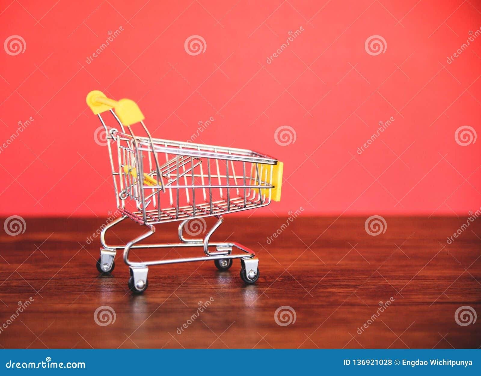 Wózek na zakupy na drewnianym, Online robić zakupy Black Friday pojęcie z żółtym wózkiem na zakupy na czerwieni/