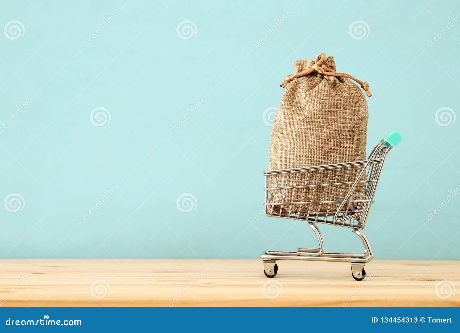 Wózek na zakupy z pełną torbą folował nad błękitnym drewnianym tłem