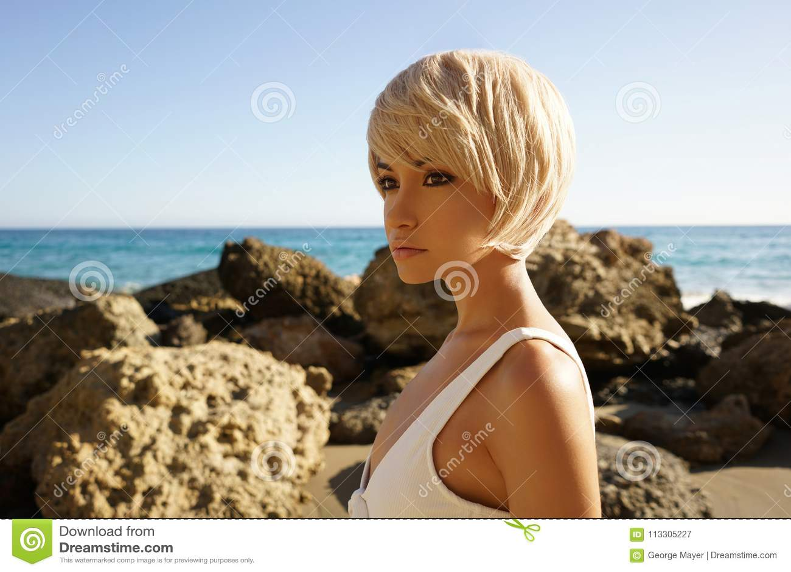 Würdevolle Frau in der weißen Badebekleidung auf dem Strand