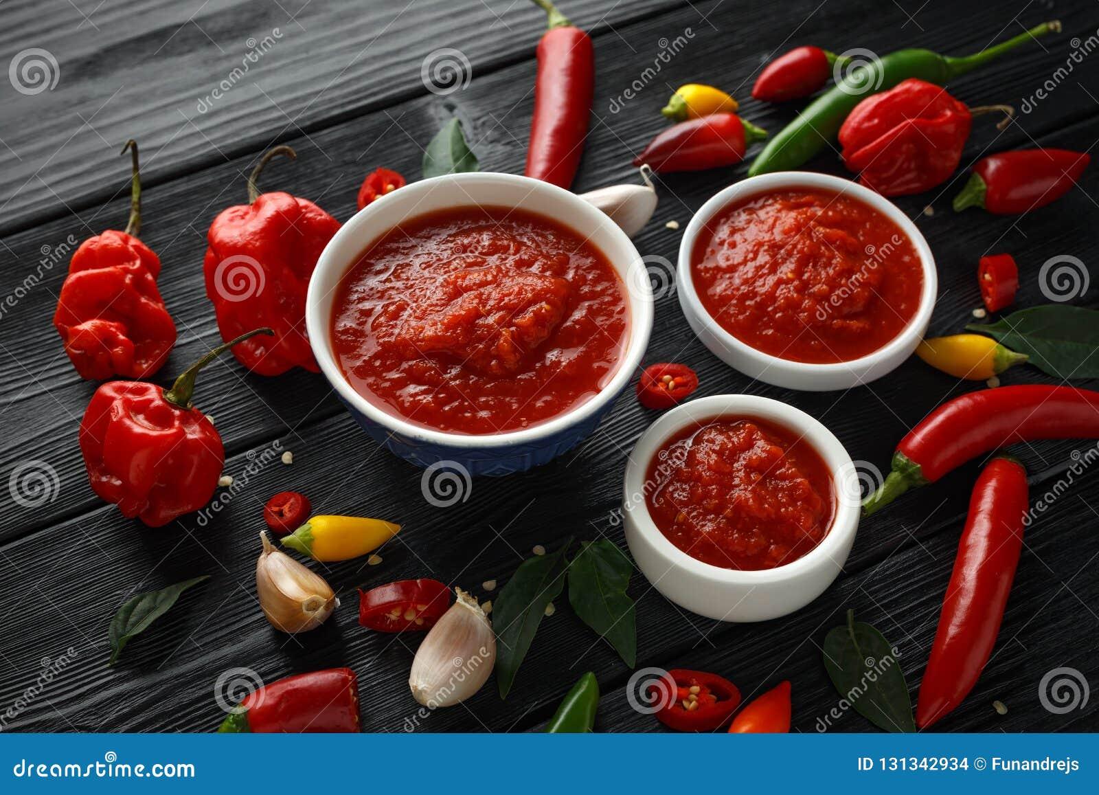 Würzige heiße süße Chili-Sauce mit Mischung des Paprikapfeffers, -knoblauchs und -tomaten auf rustikalem hölzernem Hintergrund