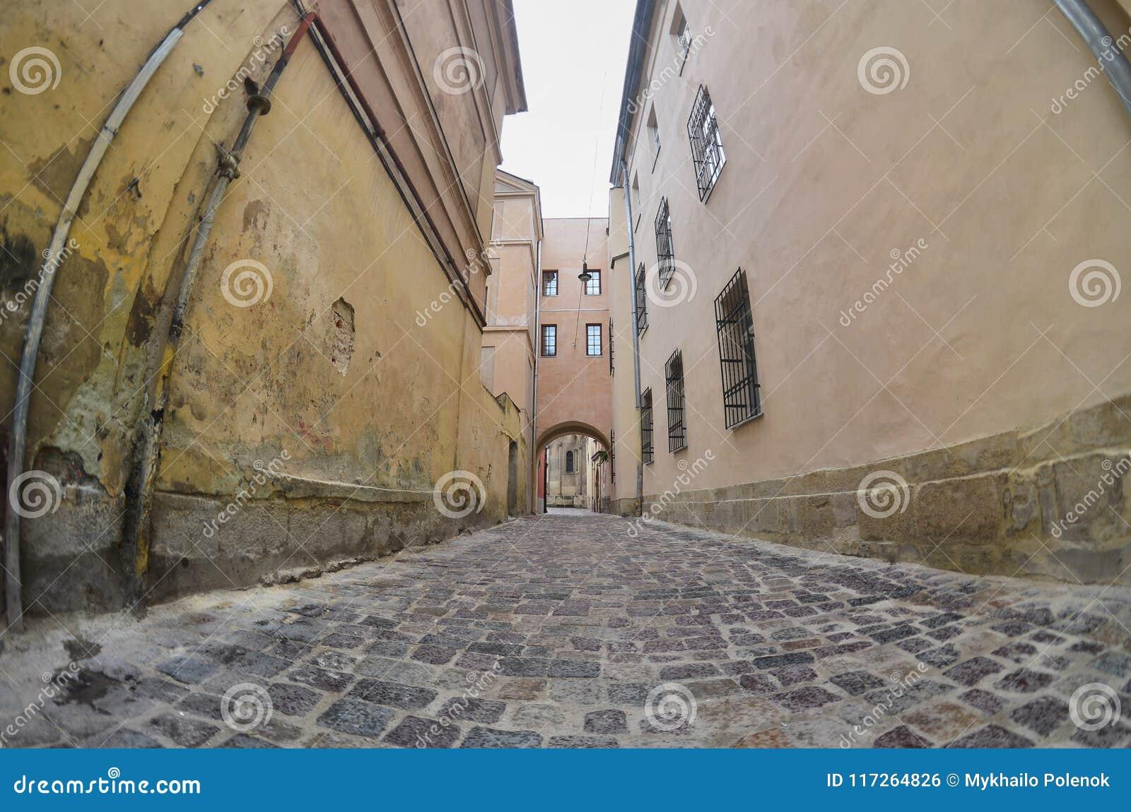 Wąska ulica z ścieżką brukowi kamienie Przejście między starymi dziejowymi wieżowami w Lviv, Ukraina