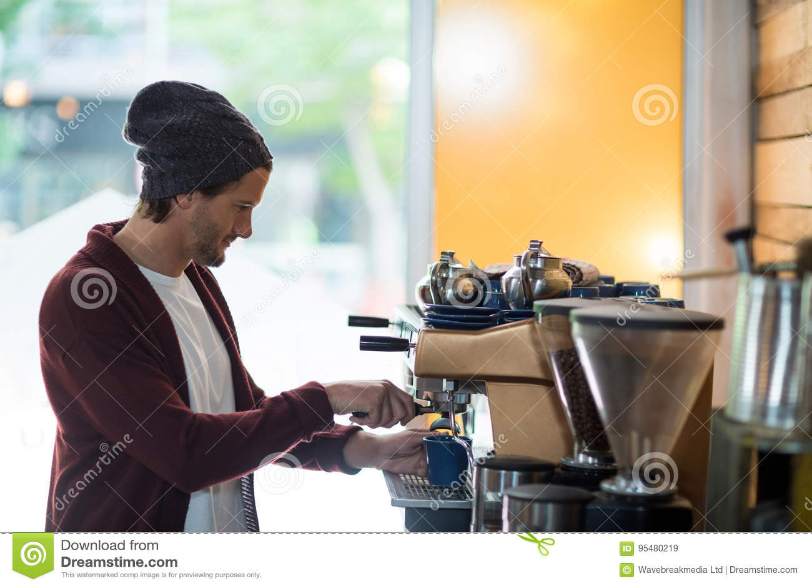 Właściciel robi filiżance kawy w kawy espresso maszynie