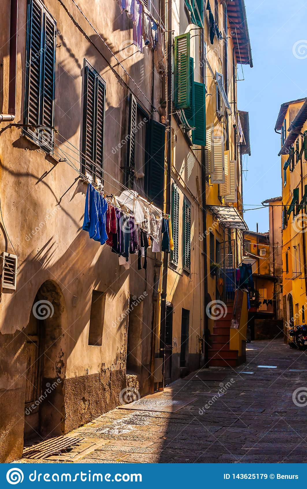 Włochy grodzka mała zwyczajna ulica częsciowo w cieniach z osuszką odzieżową i miejscowych cieniami