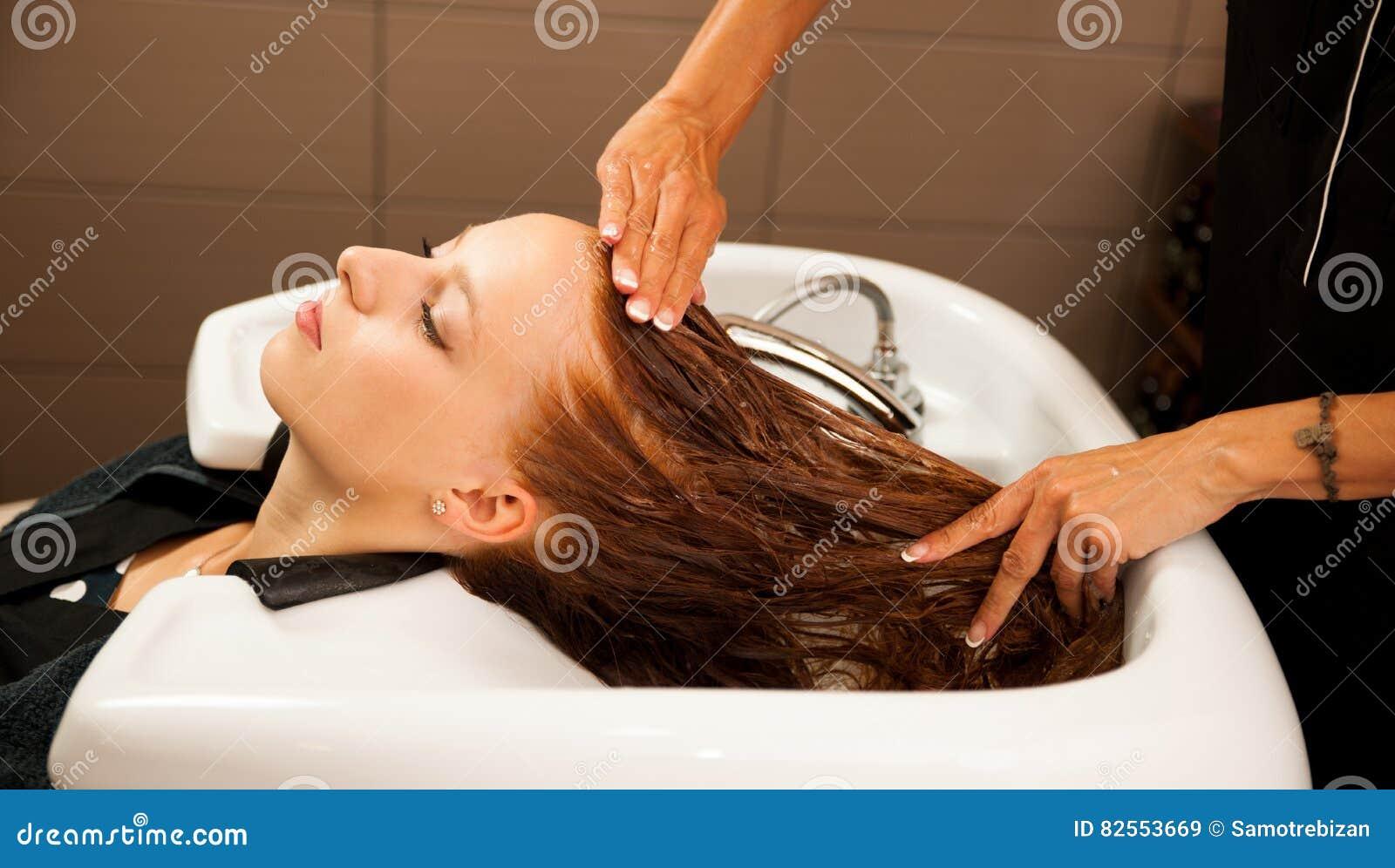 Włosiany stylista przy pracą - fryzjera płuczkowy włosy klient