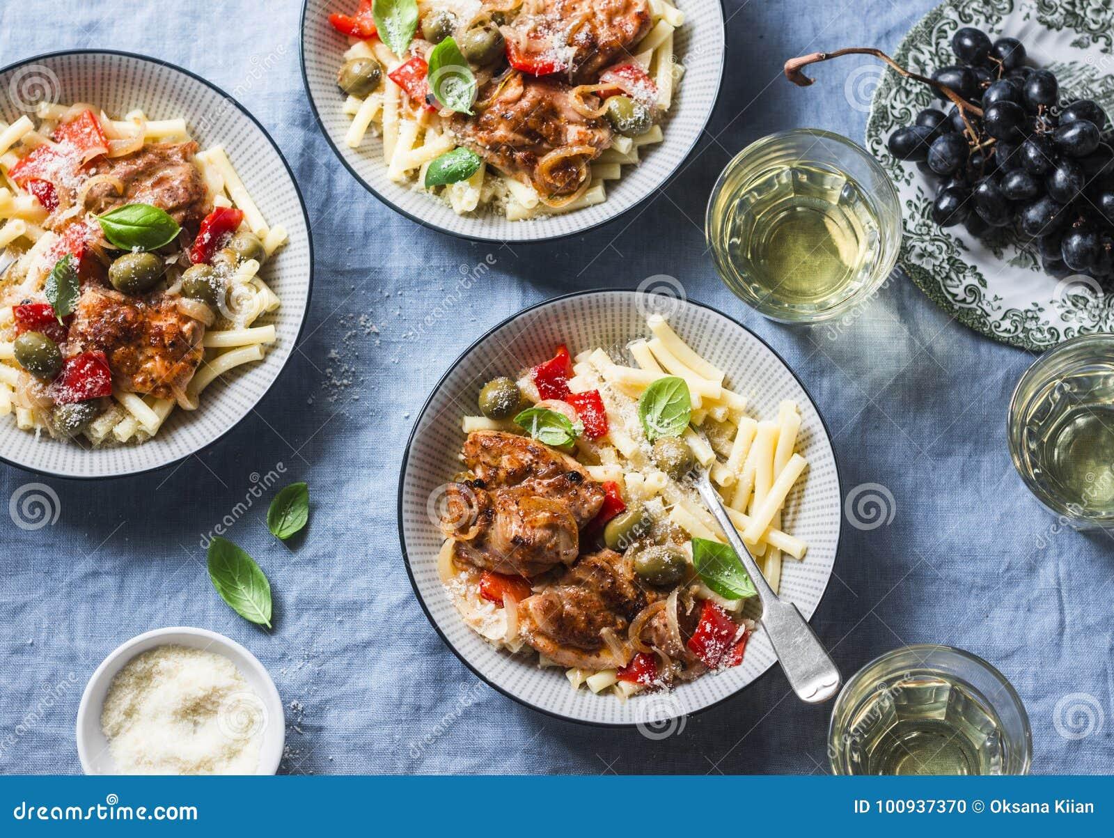 Włoski jedzenie stół Makaron z wolnym kuchenka kurczakiem z oliwkami i słodkimi pieprzami, biały wino W łyżce suchy śniadanie