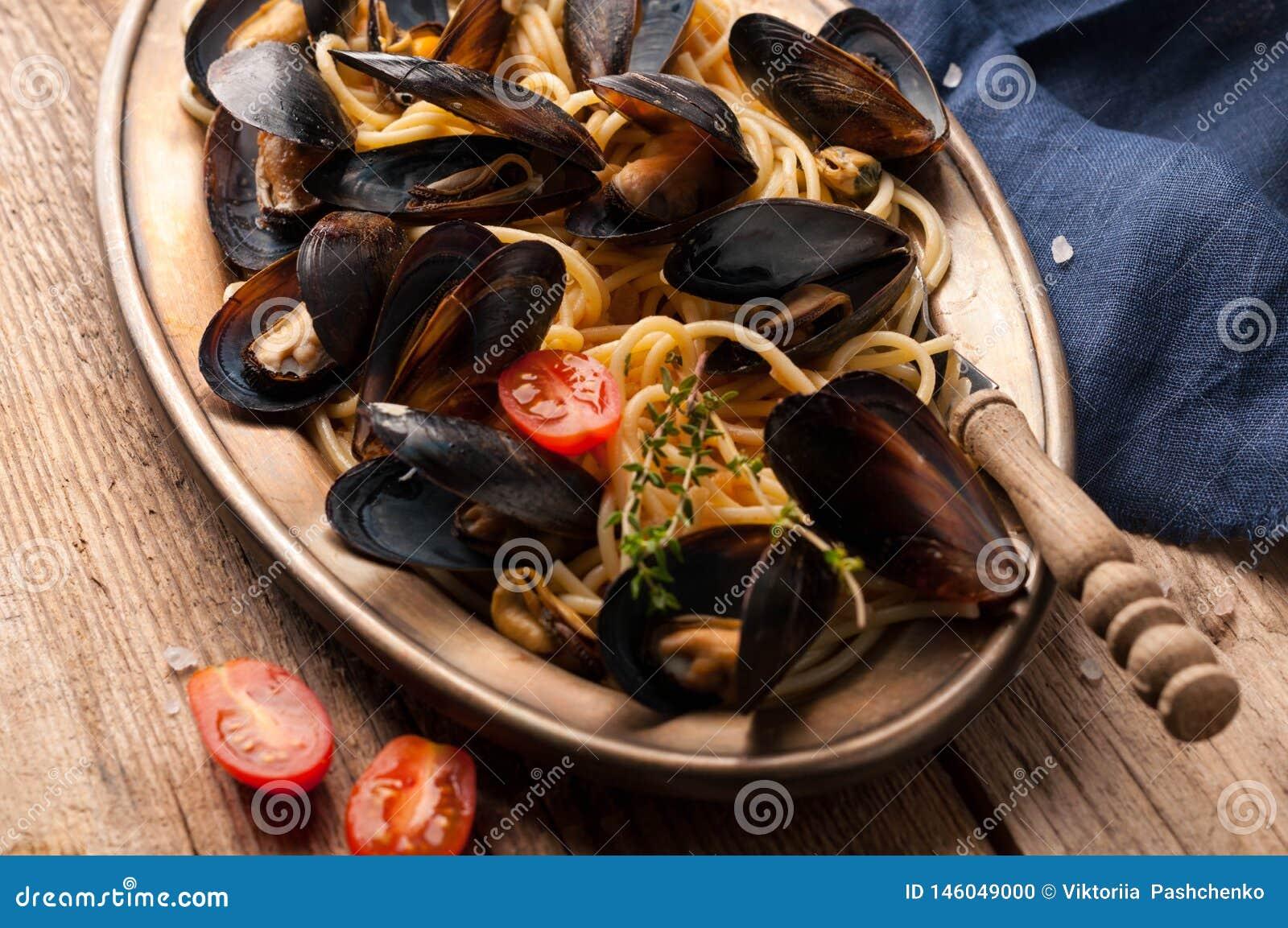 Włoski makaron z mussels w czerni skorupach i rżniętych pomidorach w metalu złotym talerzu