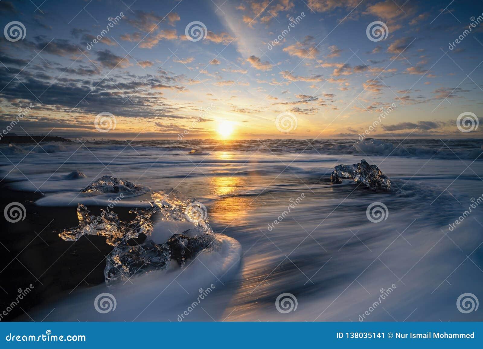 Wściekać się macha niszczących lodowych bloki przy wschód słońca na diament plaży