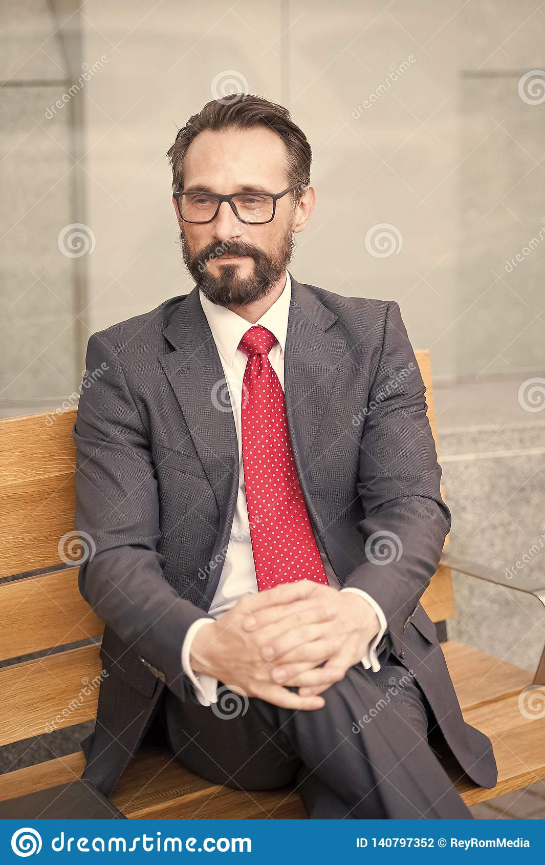 W średnim wieku biznesmen bierze relaksującą przerwę na ławce Miasta życia serie biznesowi persons Portret biznesmena obsiadanie