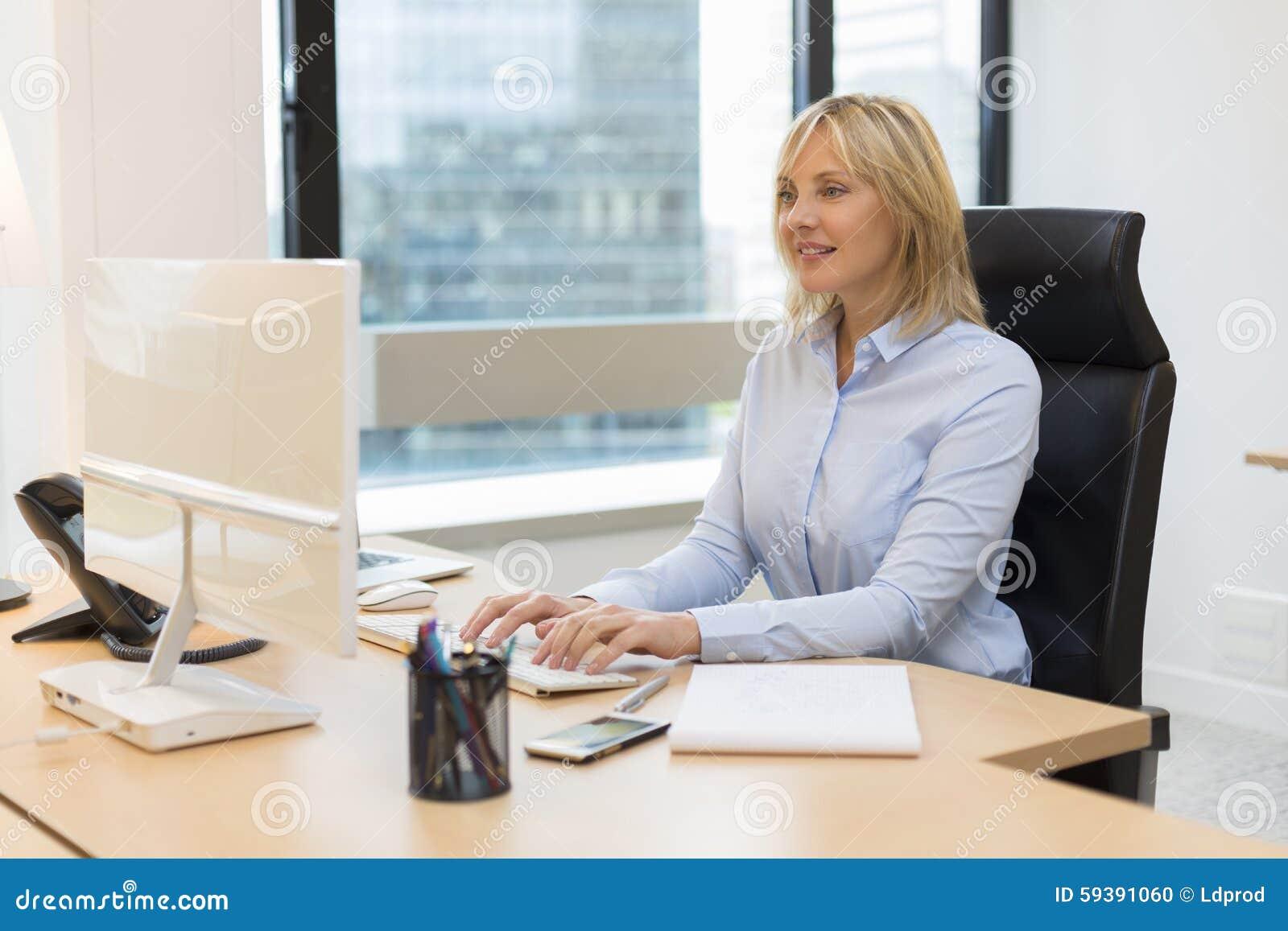 W średnim wieku biznesowa kobieta pracuje przy biurem