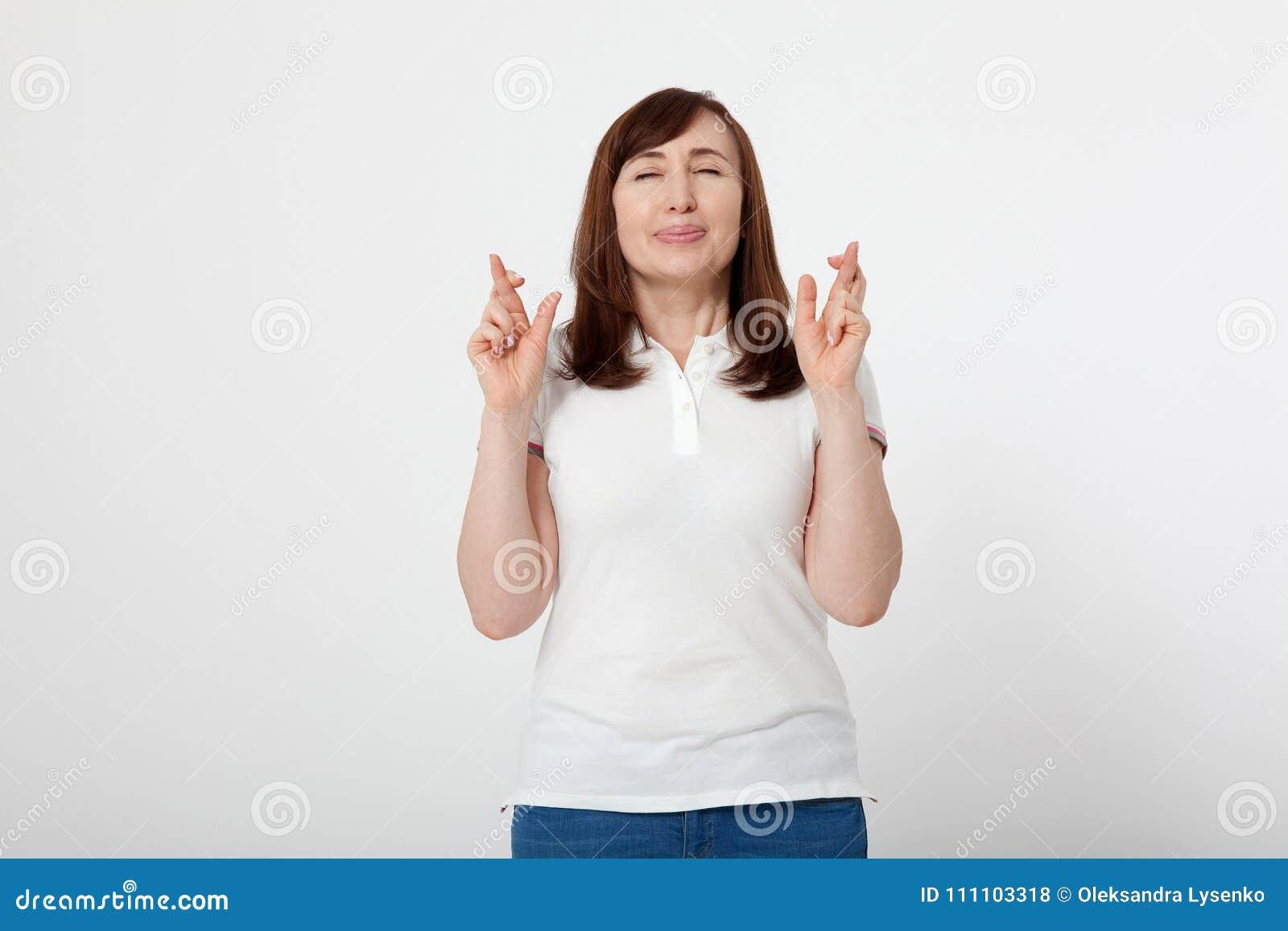 W średnim wieku kobieta krzyżuje ona i życzy na dobre szczęście palce Pusta biała koszulka, wyśmiewa up Moda stroju Macierzysty d