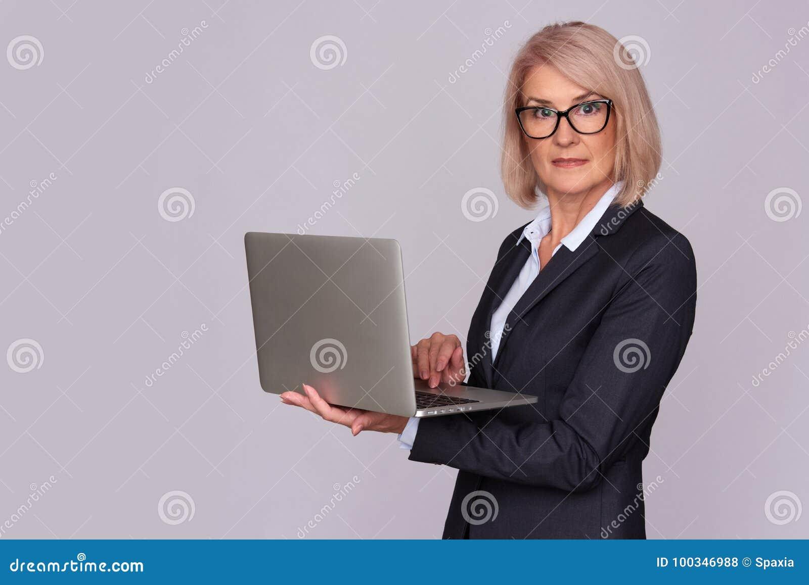 W średnim wieku kobieta pracuje na laptopie