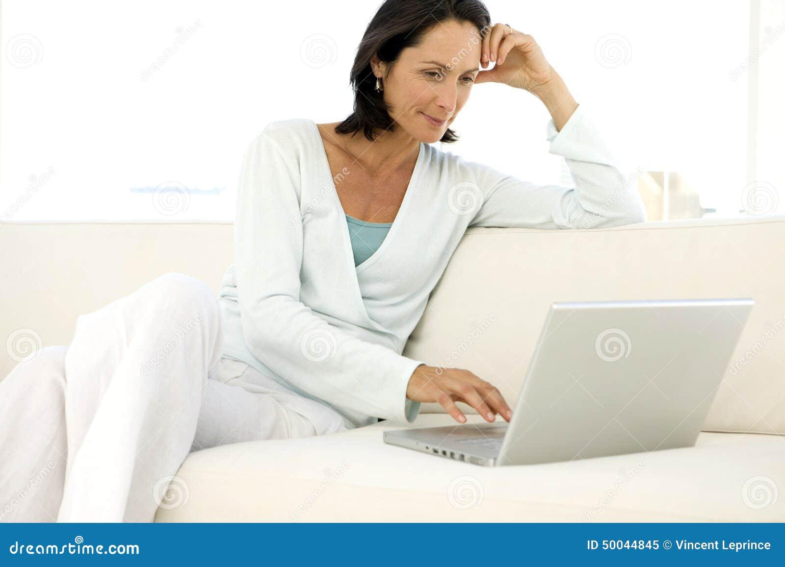 W średnim wieku kobieta używa laptop
