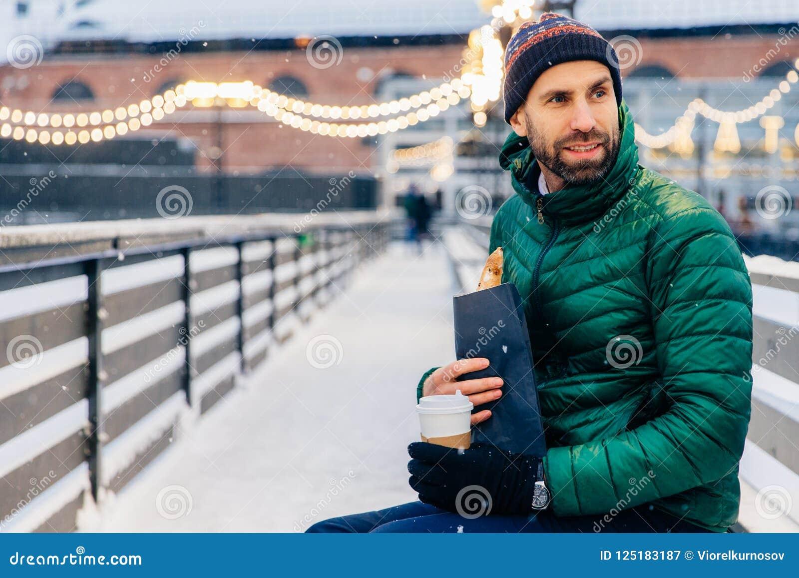 W średnim wieku mężczyzna patrzeje zamyślenie na boku, przekąski dur outdoors