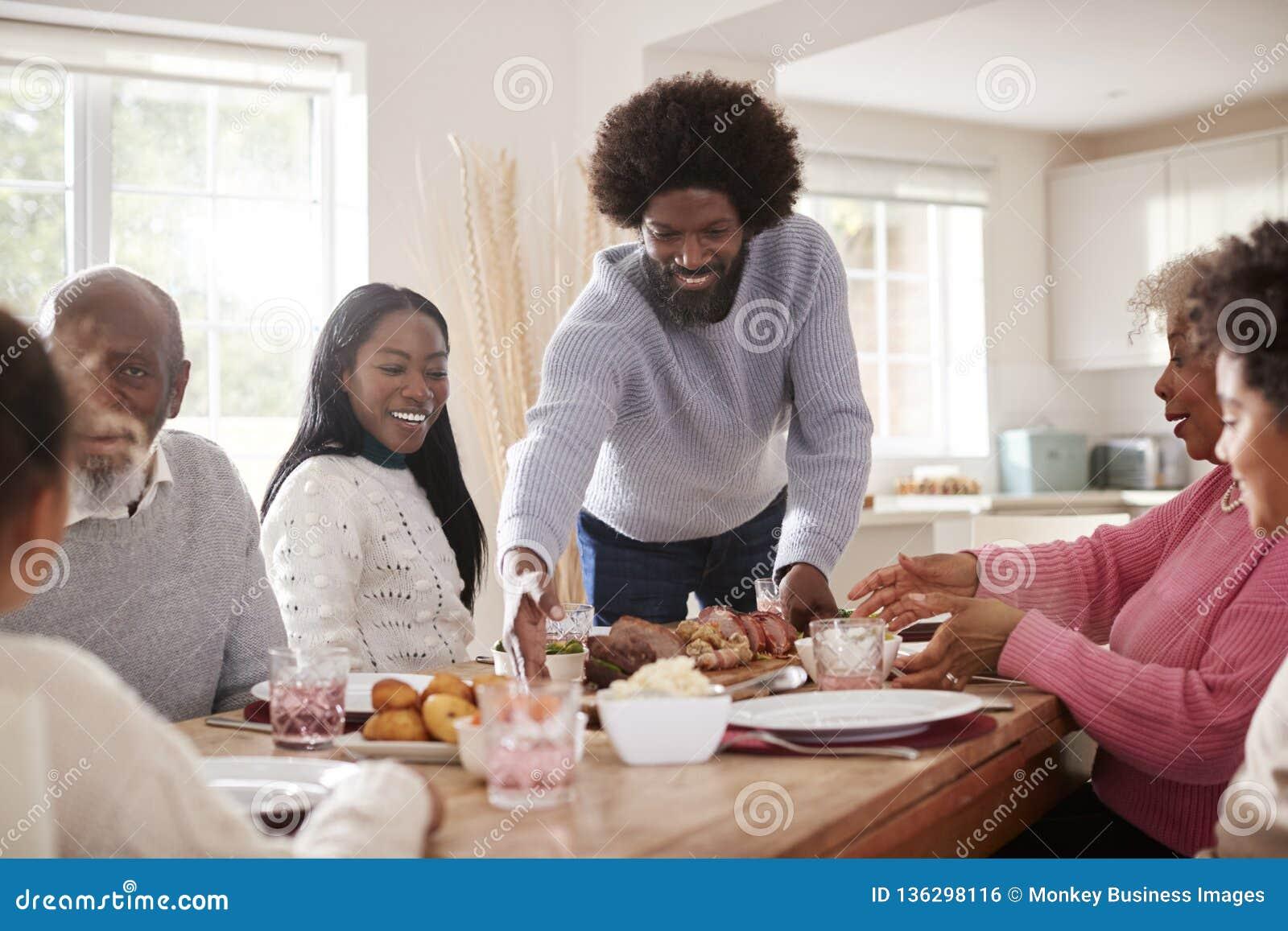 W średnim wieku murzyna dowiezienia pieczeni mięso stół dla Niedziela rodzinnego gościa restauracji z jego partnerem, dzieciakami