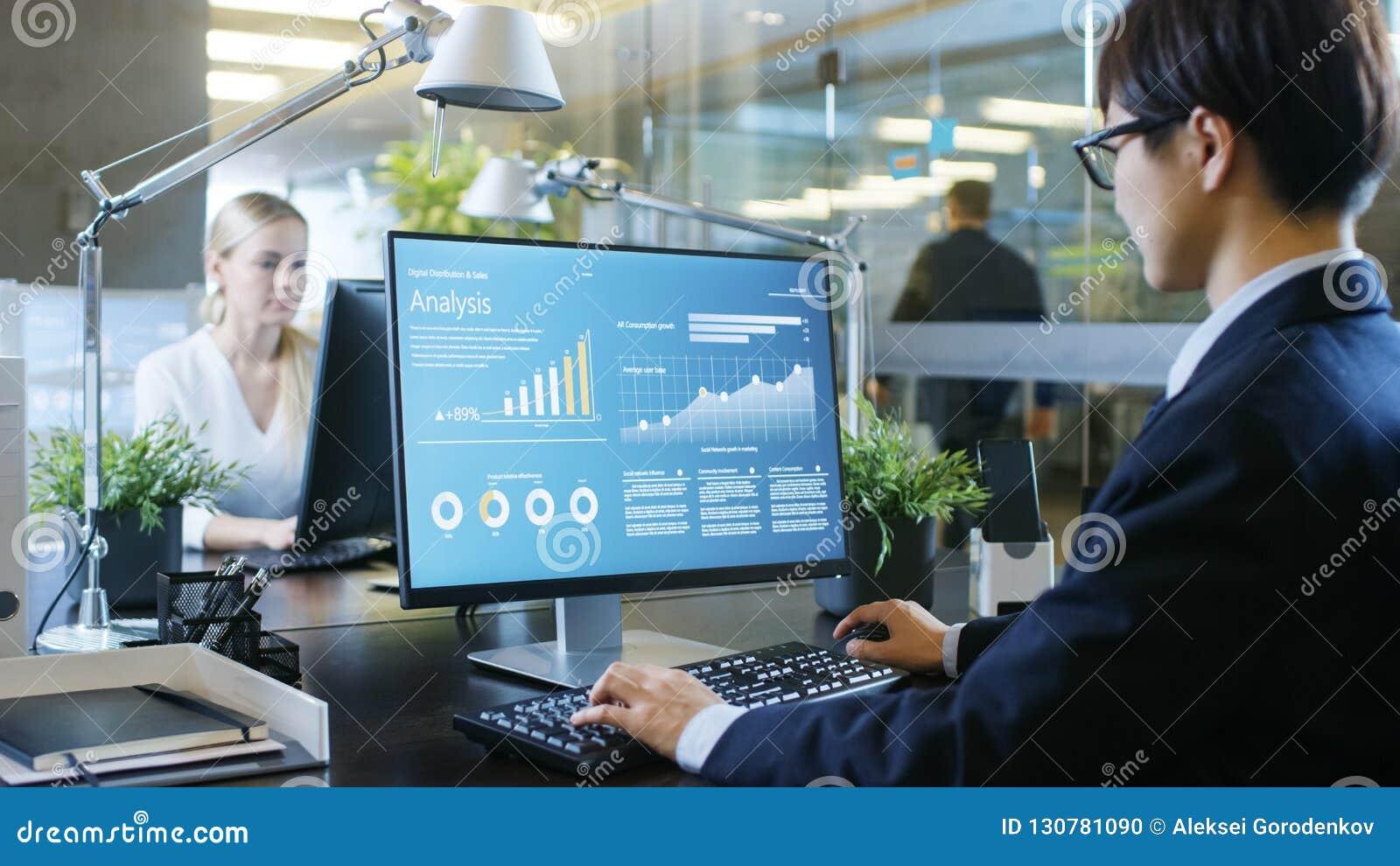 W biurze biznesmen pracuje przy Jego biurkiem, On Używa ogłoszenie towarzyskie