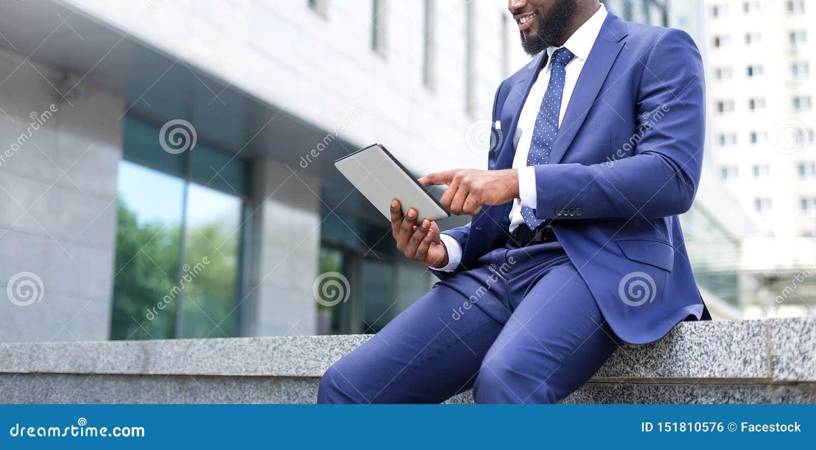 W górę afrykańskiego biznesmena używa cyfrową pastylkę podczas gdy siedzący biurowe przesłanki