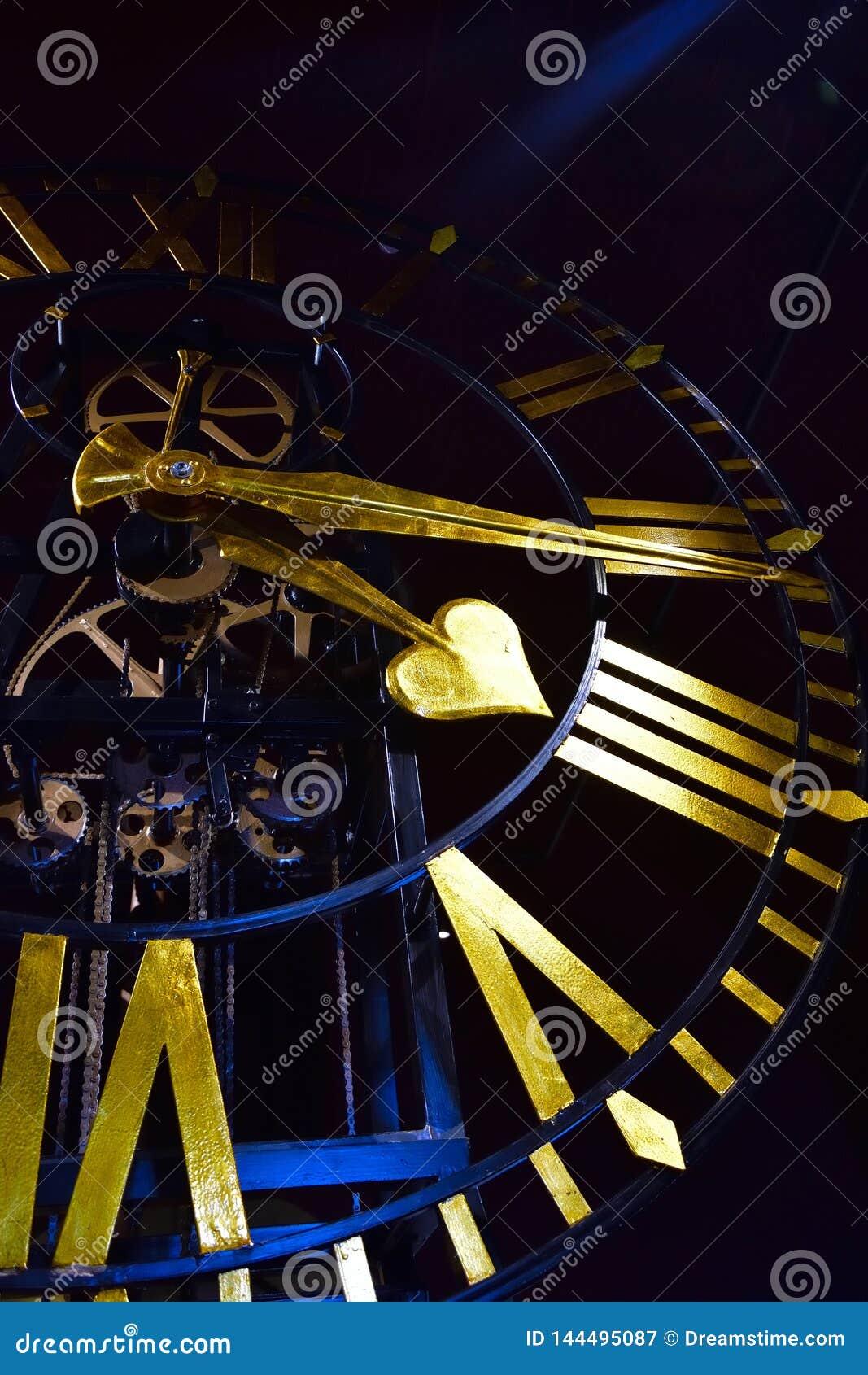 W górę antycznego ciemnego kośca zegaru z złotymi rękami i rzymskimi liczebnikami