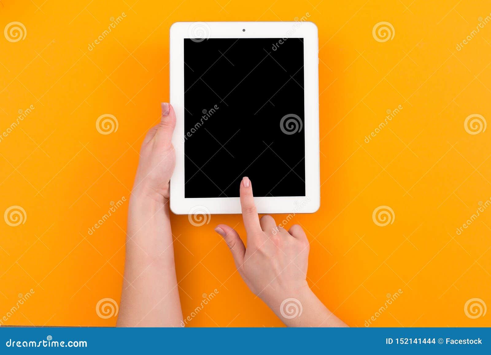 W górę odgórnego widoku trzyma cyfrową pastylkę z kopii przestrzenią na pomarańczowym tle kobieta