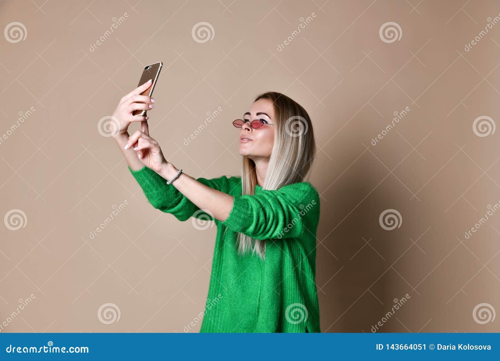 W górę portreta młoda rozochocona mody blondynki kobieta w pulowerze odzież robi selfie na smartphone, nad beżowym tłem