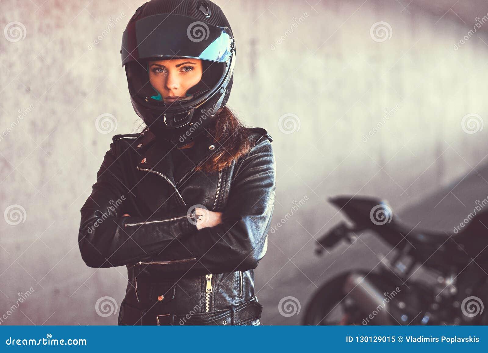 W górę portreta rowerzysta dziewczyna z jej rękami krzyżował obok jej superbike wśrodku mostu