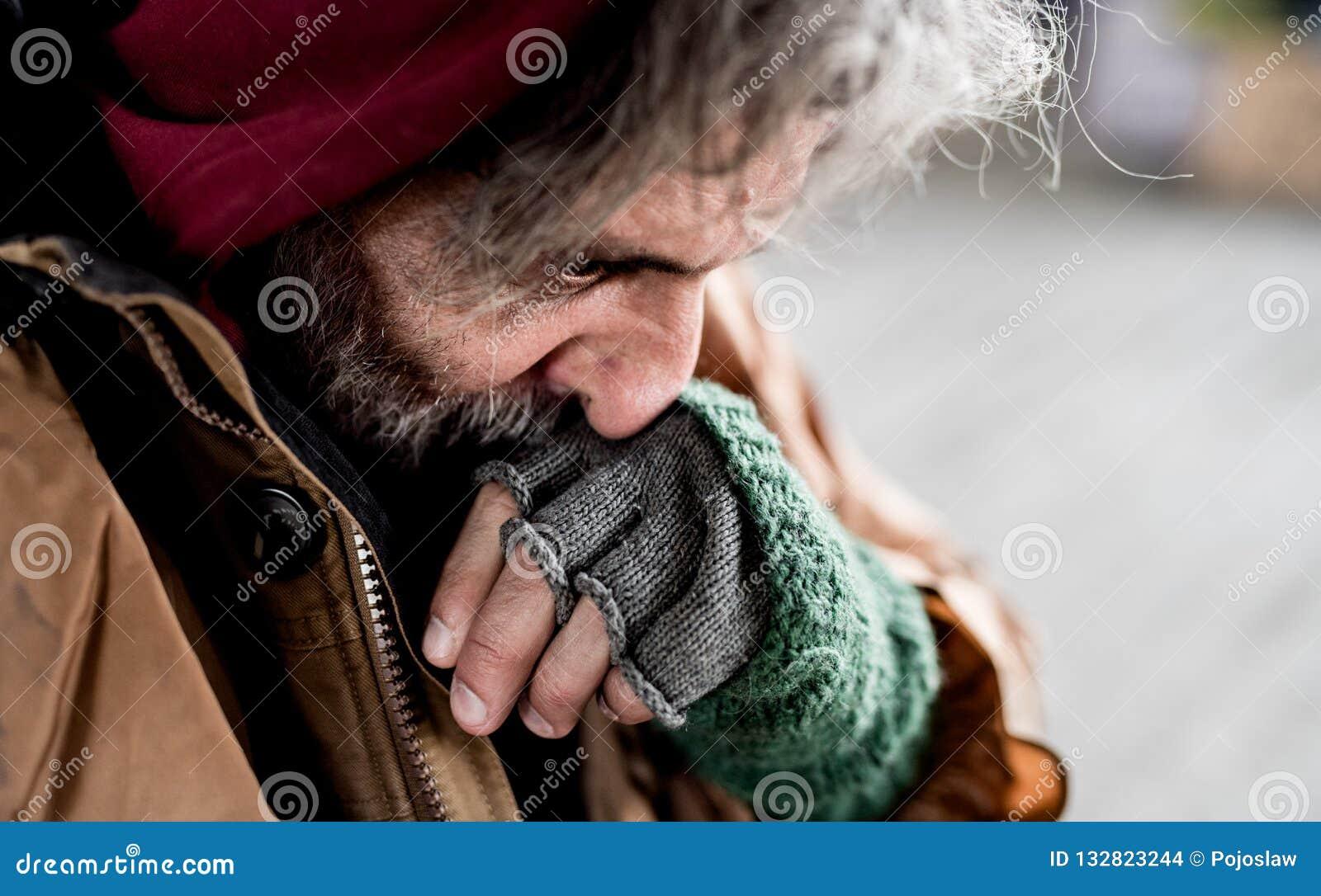A w górę widoku bezdomny żebraka mężczyzna stoi outdoors w mieście